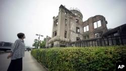 1945年原子弹爆炸幸存者公江三原目视着广岛原子弹和平纪念圆塔。
