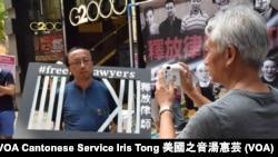 """支聯會常委梁耀忠以「即影即有」相機替支持""""一人一照片""""行動的香港大學法律系學者張達明拍照"""