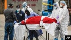 Para petugas di New York mengangkut pasien yang meninggal karena Covid-19, sementara AS kekurangan peralatan medis (31/3).