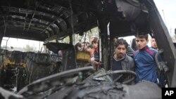بعد از انفجار بمب در بازار بغداد، مردم داخل خودروی بمبگذاری شده را نگاه می کنند.