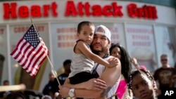 Durante las manifestaciones en Las Vegas, Ulysses Diaz sostiene a su hijo, Armani Hinton, mientras escucha los discursos sobre el veredicto del caso Zimmerman.