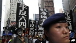 "Protesters carry placards that read ""Exonerate the June 4"" during a rally in a Hong Kong down town street Sunday, May 29, 2011, ahead of the 22nd anniversary of the June 4th military crackdown on the pro-democracy movement in Beijing. (AP Photo/Vincent Yu"