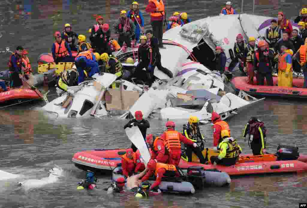 Rescue personnel in a rubber dinghy lift a passenger (bottom C) from the waters around the wreckage of a TransAsia ATR 72-600 turboprop plane that crash-landed into the Keelung river outside Taiwan's capital Taipei in New Taipei City.