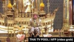 Hình ảnh chụp từ video phát trên truyền hình Thái Lan vào ngày 4 tháng 5, 2019 cho thấy Quốc vương Maha Vajiralongkorn trong phục sức hoàng gia ngồi trên ngai vàng trong lễ gia miện ở Đại Hoàng Cung ở Bangkok.