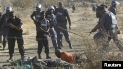 South African policemen give instructions to an injured miner after striking miners were shot outside a South African mine in Rustenburg, 100 km northwest of Johannesburg on August 16, 2012.