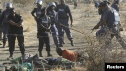 Polisi memberikan instruksi pada penambang yang terluka setelah ditembak polisi di Rustenberg, Afrika Selatan. (Foto: Reuters)