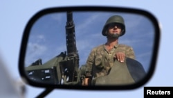 A Turkish soldier is reflected on a mirror as he stands guard on top of an armored personnel carrier on the Turkish-Syrian border near the Akcakale border crossing, October 4, 2012.