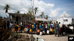 United Nations police from Bangladesh deliver drinking water to residents of Sous-Roche village, outside Les Cayes, Haiti, Oct. 11, 2016.