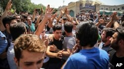 A group of protesters chant slogans at the main gate of the Grand Bazaar in Tehran, Iran, June 25, 2018.