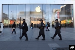 Chinese security guards march past an Apple store in Beijing, China, March 6, 2019.