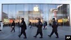 一队中国保安从北京一家苹果商店前走过。(2019年3月6日)