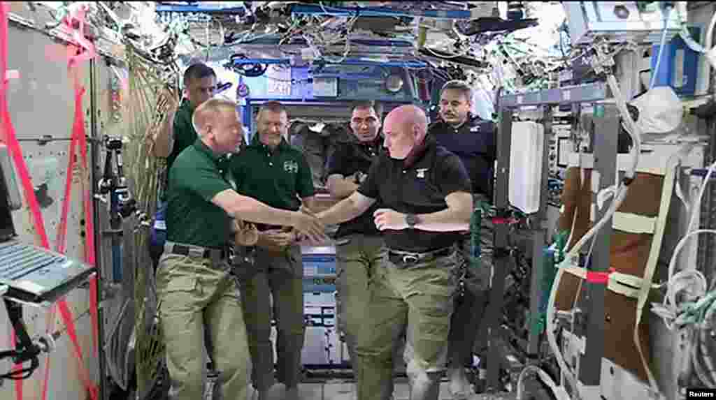 NASA astronauts Scott Kelly (R) and Tim Kopra shake hands as Kelly turns over command of the International Space Station to Kopra, Fe. 29, 2016. Kelly and Russian cosmonaut Mikhail Kornienko will land March 1 after spending a total of 340 days in space. (Credit: NASA)