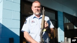 In this Aug. 31, 2019, photo. Police Senior Sgt. Braydon Lenihan poses holding a banned gun that has been bent by a hydraulic machine outside a temporary gun collection venue in Porirua, near Wellington, New Zealand. (AP photo/Nick Perry)