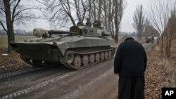 Un sacerdote saluda mientras un tanque separatista aparentemente regresa a su base, cerca de Donetsk.