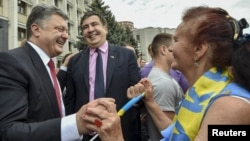 FILE - Ukrainian President Petro Poroshenko, left, and former Georgian President Mikheil Saakashvili, who now is governor of the Odessa oblast, are greeted by a local resident near the regional state administration in Odessa, May 30, 2015.