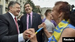 Ukrainian President Petro Poroshenko, left, and then-governor of Odessa region Mikheil Saakashvili, center, are greeted by a local resident near the regional state administration in Odessa, Ukraine, May 30, 2015.