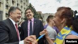 乌克兰总统波罗申科(左)和敖德萨州长萨卡什维利(中)与当地居民交谈(资料照)