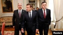 Presiden Perancis Emmanuel Macron (tengah) berjalan bersama PM LIbya Fayez al-Sarraj (kanan) dan Jenderal Khalifa Haftar sebelum pertemuan di Paris, Selasa (25/7).