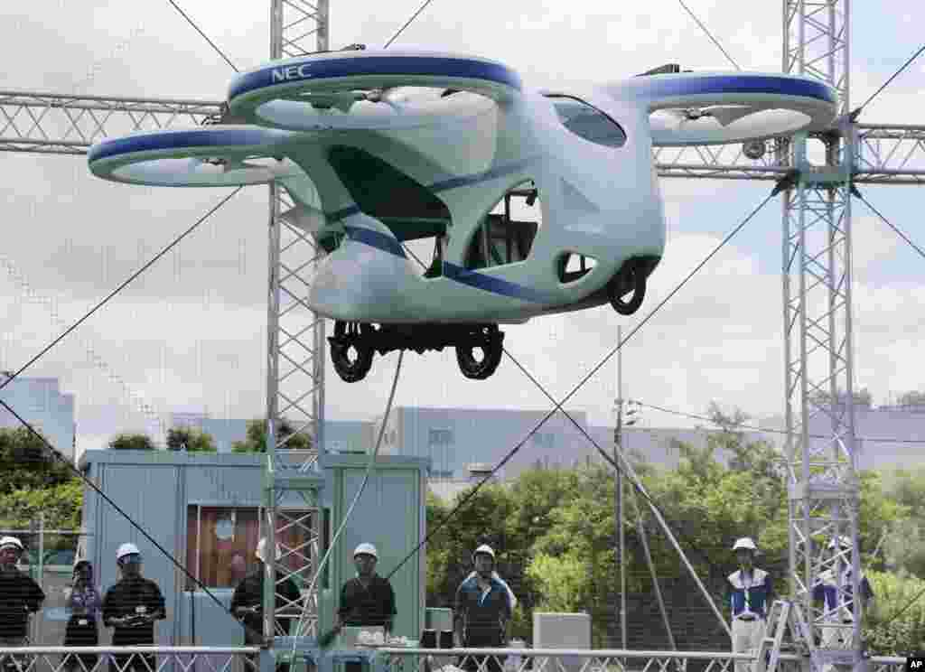 "NEC Corp.'s machine with propellers hovers at the company's facility in Abiko near Tokyo, Japan. The Japanese electronics maker showed a ""flying car,"" a large drone-like machine with four propellers that hovered steadily for about a minute."