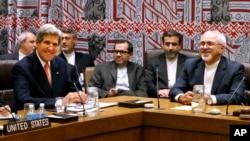 Le secrétaire d'Etat américain John Kerry (g.) et le ministre des Affaires étrangères iranien Javad Zarif (d.), assistant à une réunion des cinq membres permanents du Conseil de sécurité plus l'Allemagne lors de la 68e session de la Assemblée générale des Nations Unies au siège de l'ONU à New York, 26 septembre 2013.