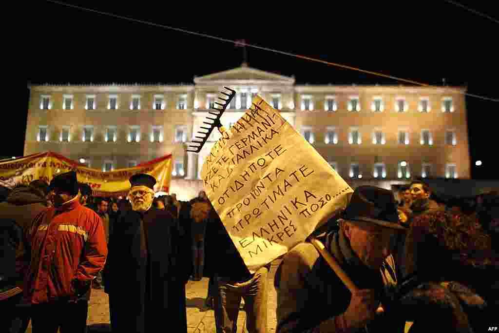 Một người biểu tình treo biểu ngữ trên một cái cào đất nói chuyện với một người biểu tình khác tại quảng trường Syntagma, trước mặt Quốc hội ở Athens, 19 tháng 2, 2012. (AP)