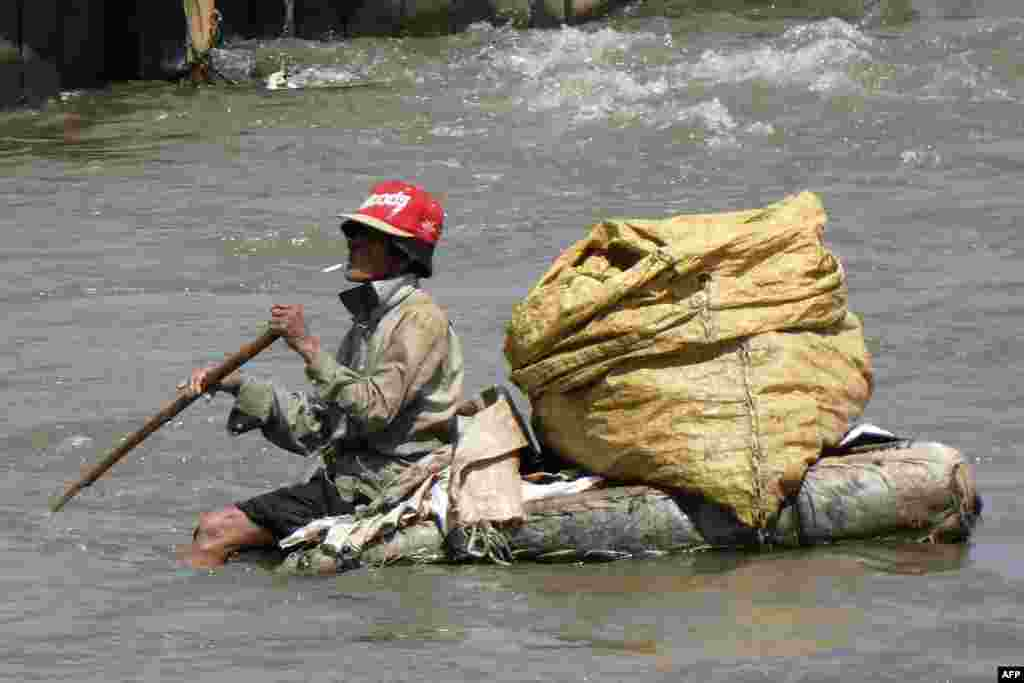 A scavenger sits on a raft as he attempts to collect recyclable materials in a river in downtown Jakarta, Indonesia.