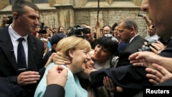 A woman tries to kiss German Chancellor Angela Merkel after she visited the Srebrenica exhibition in downtown of Sarajevo, Bosnia and Herzegovina, July 9, 2015.