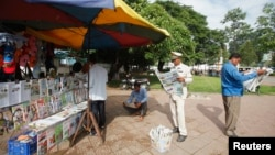 FILE - People read newspapers at a street side stand in central Phnom Penh.
