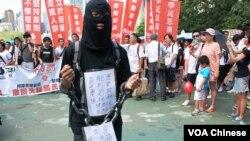 參加729反洗腦國民教育大遊行的示威者身穿黑衣、戴上鎖鏈,喻意國民教育黑箱作業,箝制學生思想