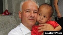 Ông Kim Hartzner bế một bé trai tại một viện mồ côi ở Haeju, Bắc Triều Tiên