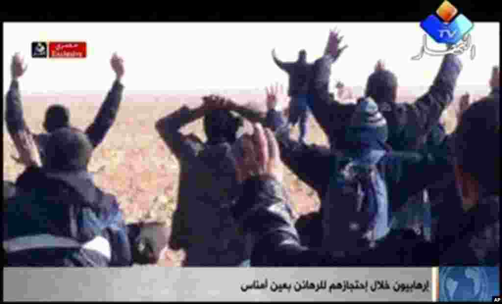 "In this image made from video, a group of people believed to be hostages kneel in the sand with their hands in the air at an unknown location in Algeria. An Algerian security official says de-mining squads searching for explosives found ""numerous"" bodies Sunday, Jan. 20, 2012 at a gas refinery where Islamic militants took dozens of foreign workers hostage."