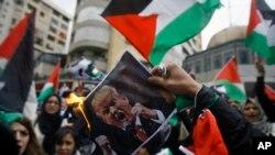 Etidyan libanè ak palestinyen ki tap boule yon poster Prezidan Donald Trump pandan yo tap patisipe nan yon manifestasyon nan vil Sidon, pati sid peyi Liban. (Dat: 7 desanm 2017).
