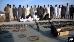 FILE - Arrested suspects and recovered weapons are displayed for the media by Pakistani paramilitary forces following a search operation in Shah Kass, an area of Pakistan's Khyber tribal region along the country's border with Afghanistan, March 3, 2017.