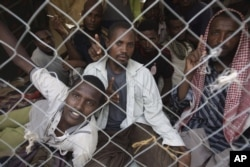 Ethiopian migrants look through a fence as they wait to be evacuated at a departure center in the western Yemeni town of Haradh, on the border with Saudi Arabia and Yemen, Wednesday, March 21, 2012.