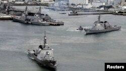 共同社的照片显示日本海上自卫队的驱逐舰开出日本南部的基地。