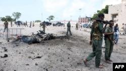 Petugas keamana Somalia berjalan melewati mobil yang hancur akibat ledakan bom di gedung parlemen di luar gedung parlemen Somalia di Mogadishu (5/7).