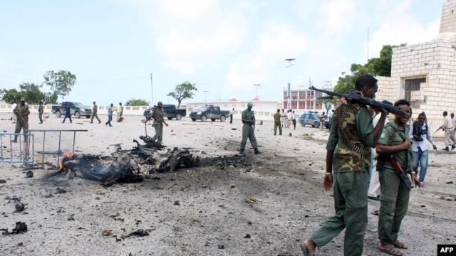 Somalian security forces walk past the remains of a car after it exploded outside Somali parliament building, Mogadishu, July 5, 2014.