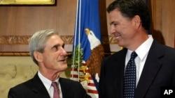El exdirector del FBI, James Comey (derecha), conversa con su predecesor, Robert Mueller, en esta foto de archivo del 4 de septiembre de 2013, cuando Comey fue juramentado.