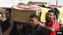 Warga menggotong peti jenazah korban pengeboman di distrik Ur, Baghdad, Irak, Jumat (28/10).