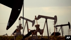 Pumpjacks bob in a field near Lovington, N.M. World oil prices, which have been declining, fell further Monday when Iran restated its plan to increase crude exports.