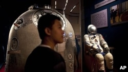In this July 6, 2011 photo, a visitor stands near the Shenzhou 5 re-entry capsule, that was used in China's first human spaceflight mission, and the the space suit worn by crew member Yang Liwei at an exhibition in Beijing, China.
