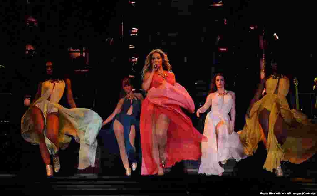 Beyoncé junto a las bailarinas, lucen todas trajes largos de colores tras uno de los numerosos cambios de vestuario que se dan a lo largo de los conciertos de la artista.