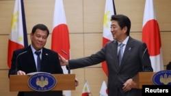 26일 일본 도쿄 총리관저에서 진행된 정상회담 직후 합동기자회견에서 웃고 있는 로드리고 두테르테(왼쪽) 필리핀 대통령과 아베 신조 총리.