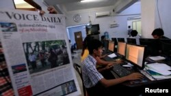 Journalist holds up a sample copy of The Voice Daily newspaper at a news room in Rangoon, March 31, 2013.