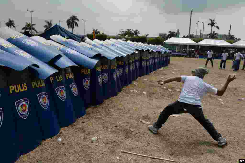 A mock protester throws a water bomb during police exercises to manage civil unrest in Manila, Philippines ahead of a visit by US President Barack Obama.