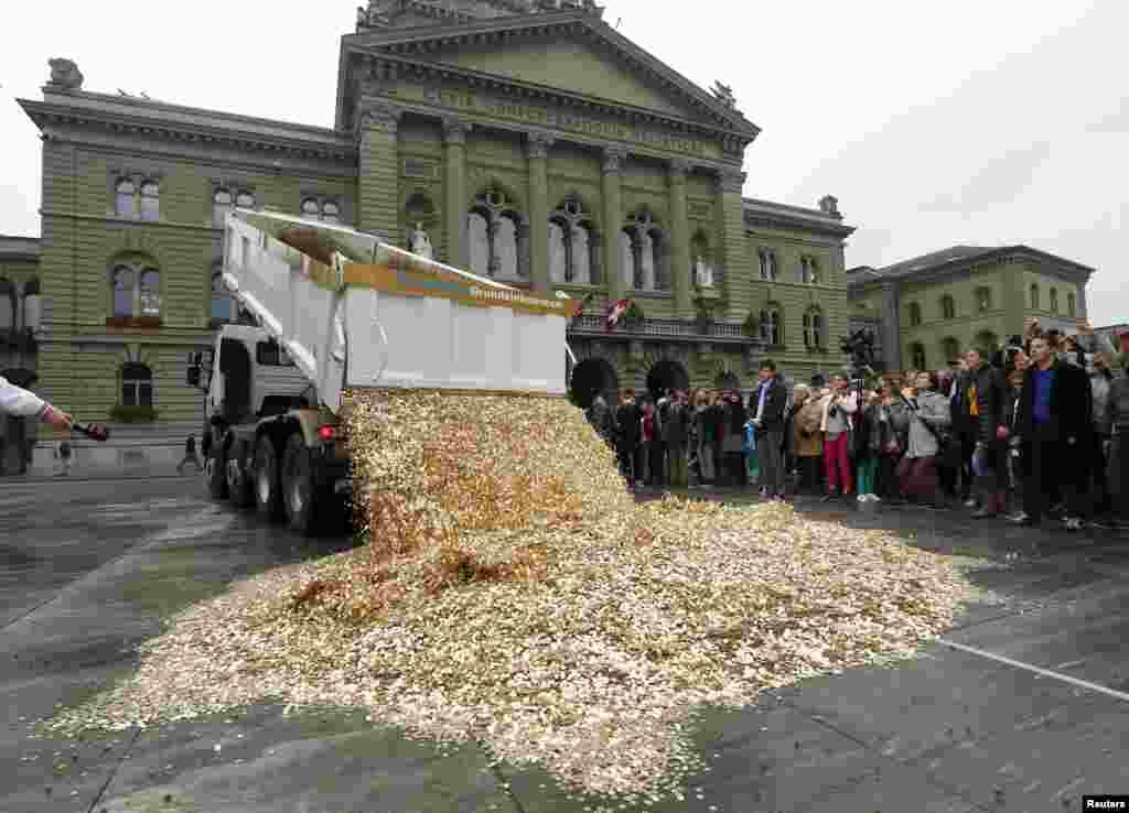 4일 스위스 베른에서 열린 행사에서 5라펜짜리 동전을 가득 실은 트럭이 동전을 쏟아놓고 있다. 이번 행사는 스위스 가구의 최소 수입 보장을 촉구하는 위원회 주최로 열렸다.