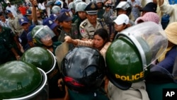 Tep Vanny, rear center, of Boeung Kak lake, scuffles with riot police officers during a protest rally against land eviction near the prime minister's residence, in Phnom Penh, file photo.