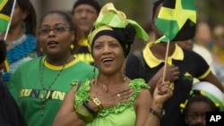 Pauline Brown waves her country's flag at the 50th anniversary of Jamaica's independence celebration in Miramar, Fla. Aug. 6, 2012.