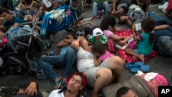 Members of a US-bound migrant caravan rest on a road between the Mexican states of Chiapas and Oaxaca after federal police briefly blocked them outside the town of Arriaga, Oct. 27, 2018.