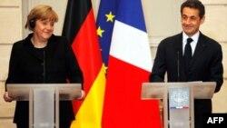 Angela Merkel ve Nicolas Sarkozy, Pazartesi günü Paris'teki basın toplantısında gazetecilerin sorularını yanıtlarken